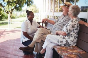 residents sitting on bench with nurse