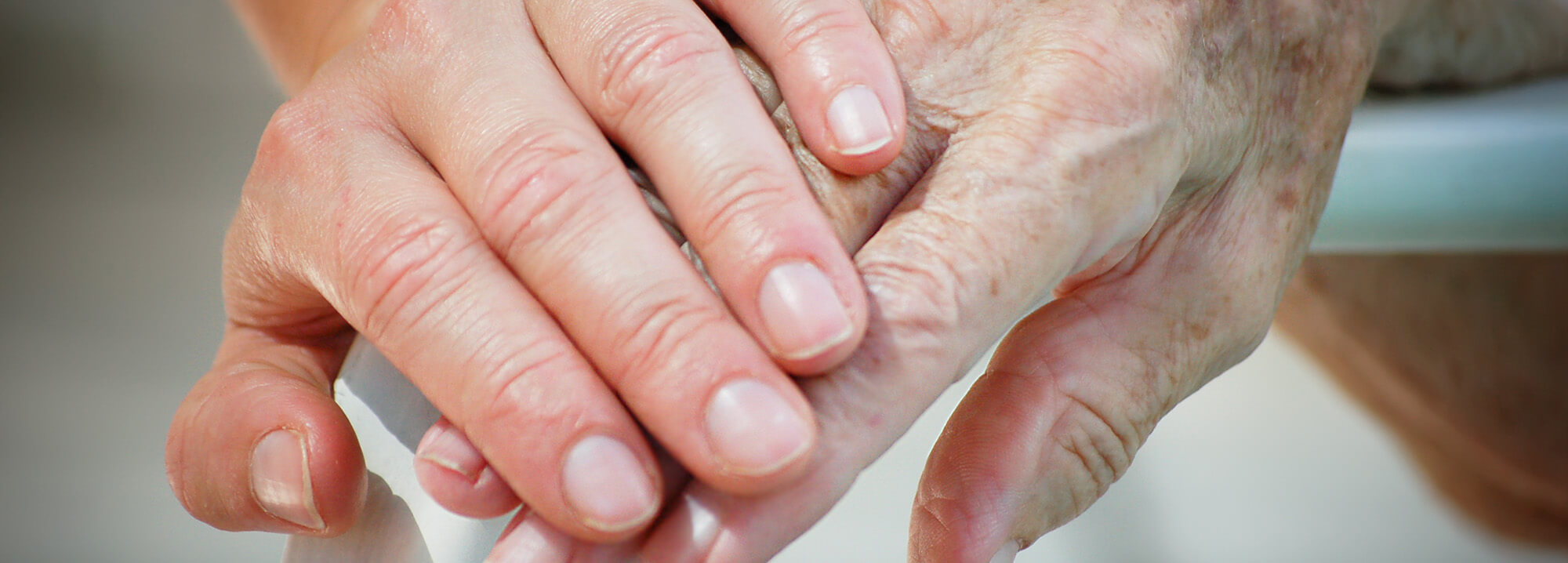 a younger hand over an older hand